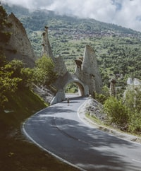 man walking on road near arch