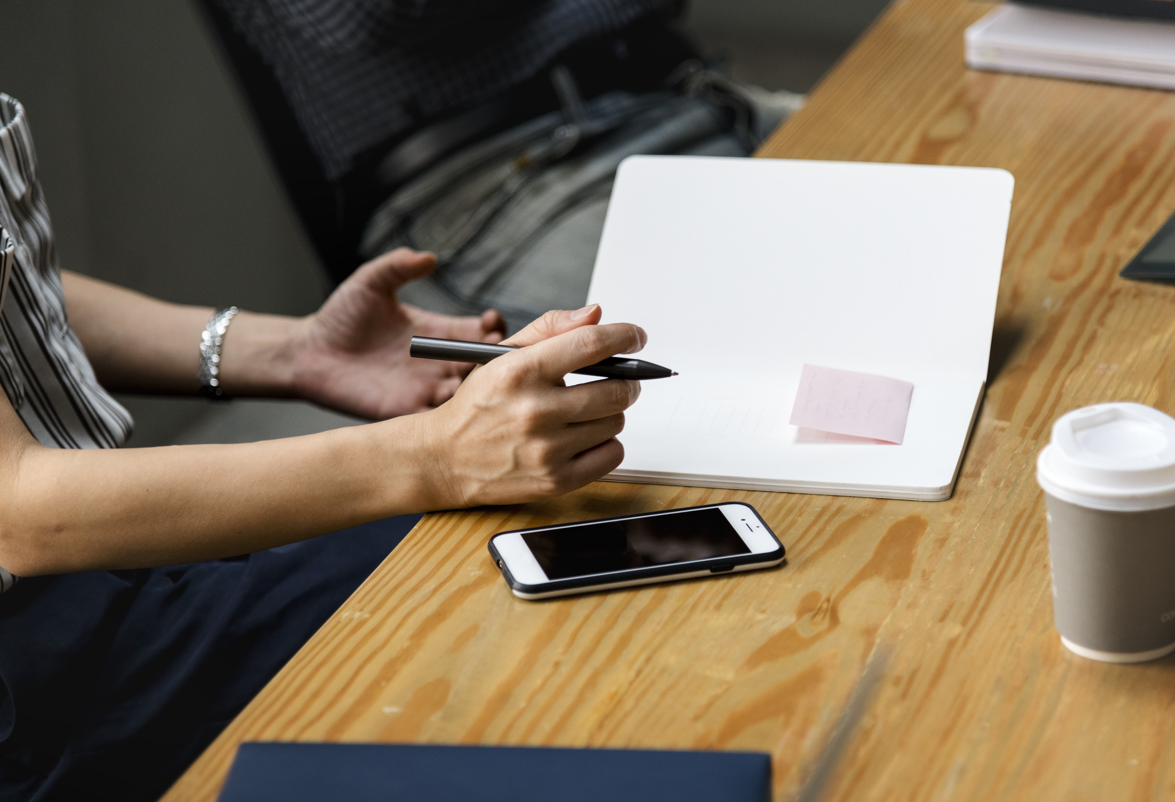person holding pen on table with notebook and iPhone