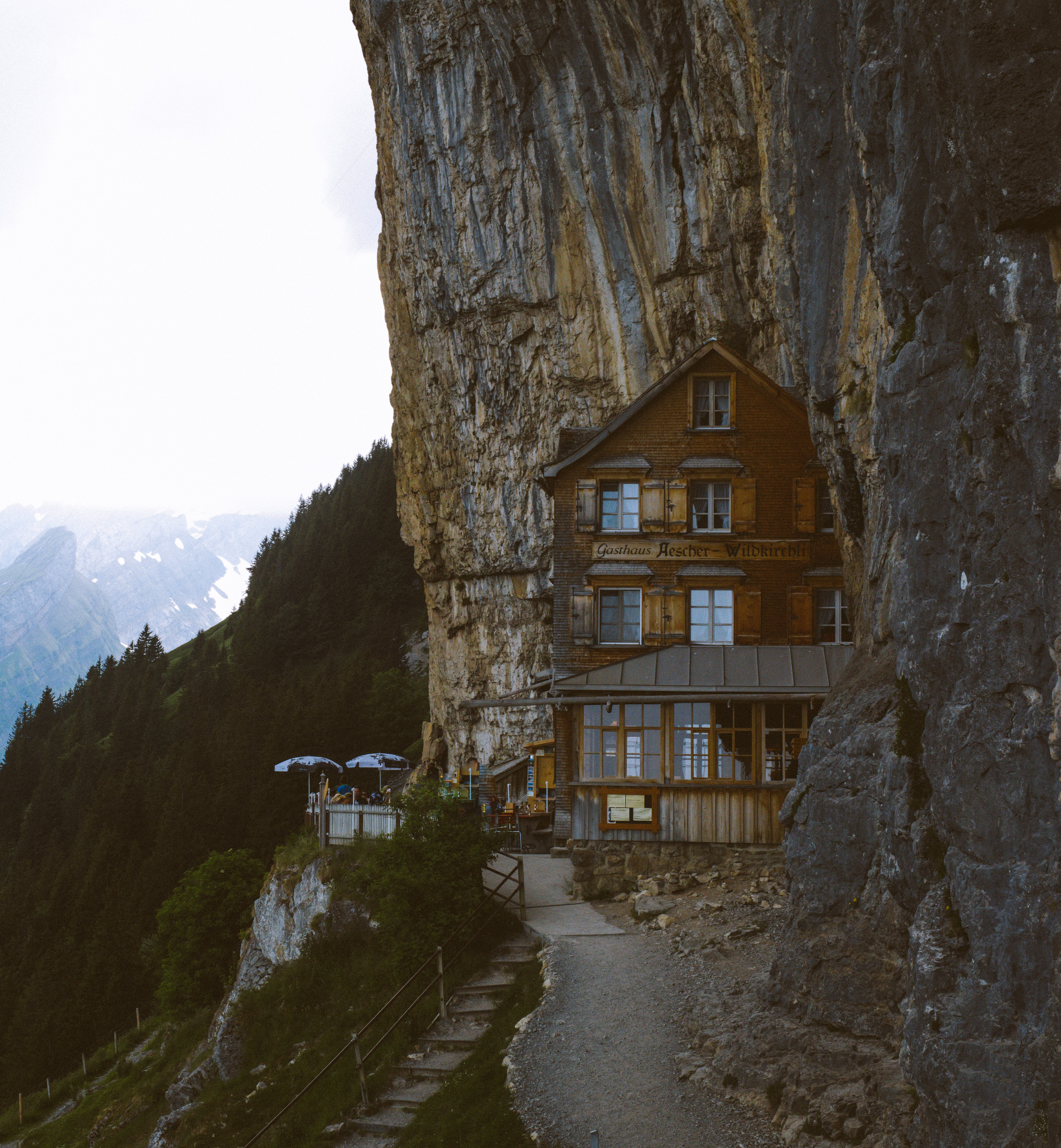 brown wooden house beside cliff