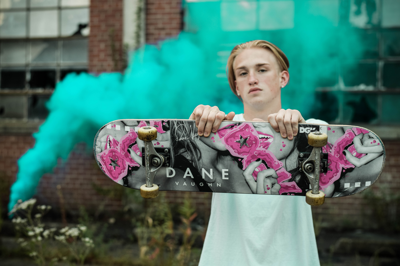 man holding gray and pink Dane skateboard