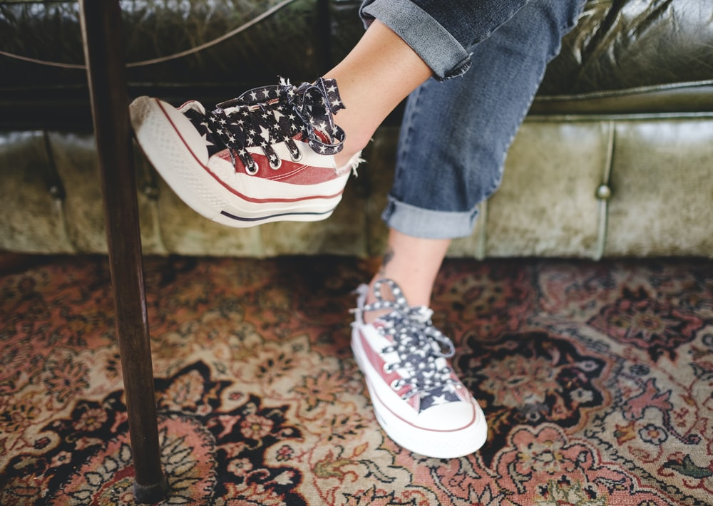 woman in red-and-white sneakers and blue jeans