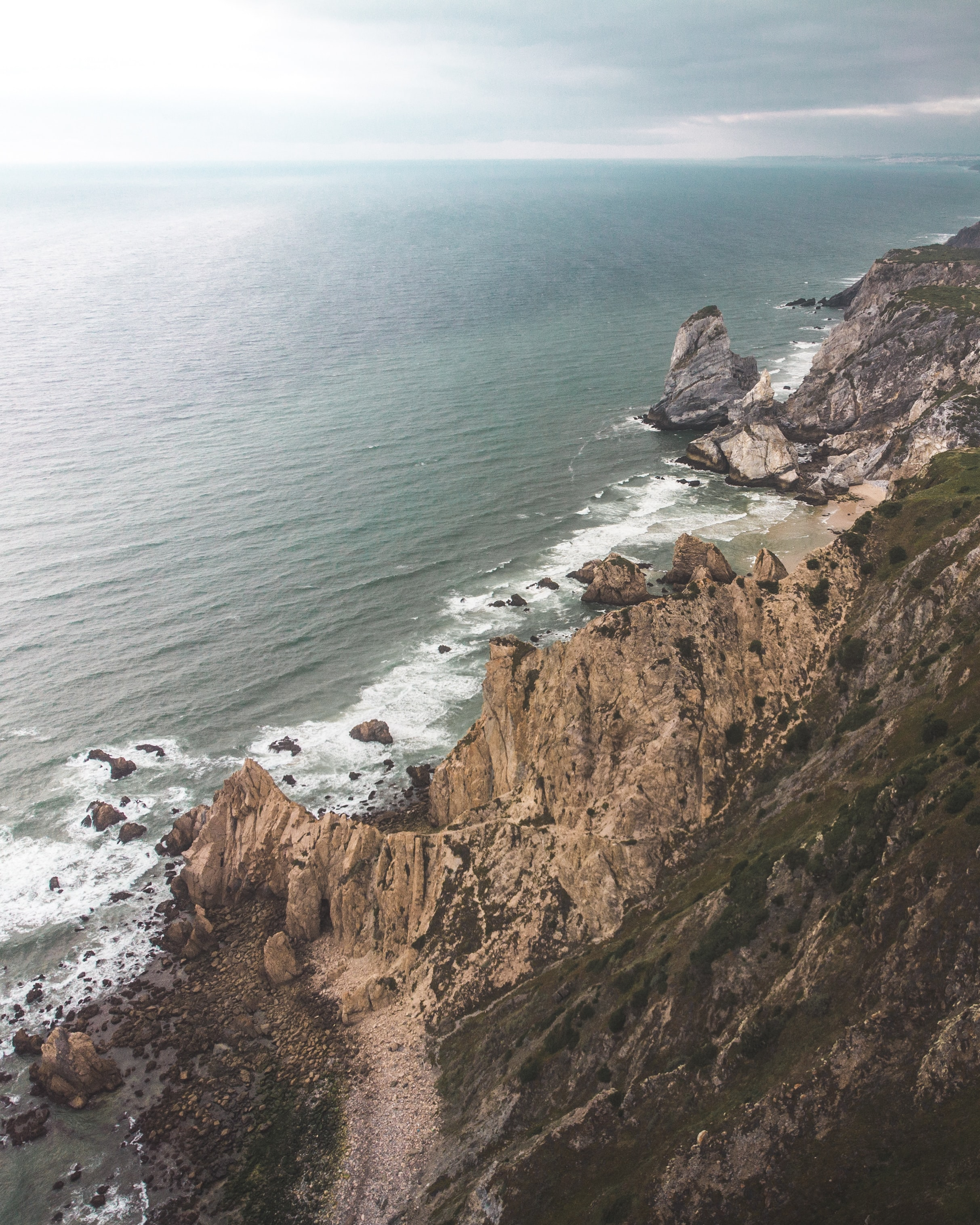 bird's-eye view photo of seashore and cliffs during daytime