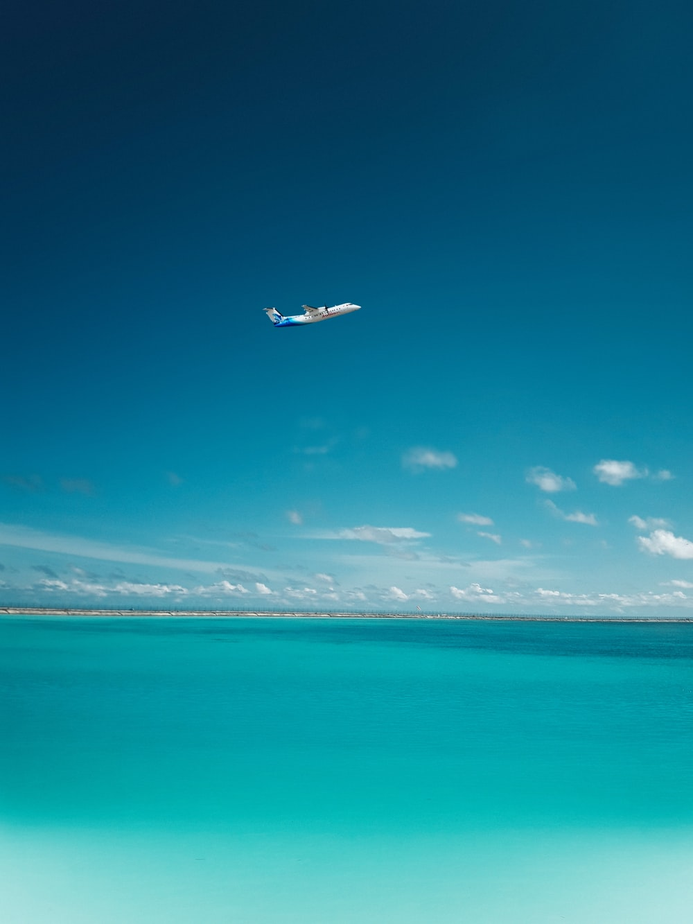 photo of airplane over body of water