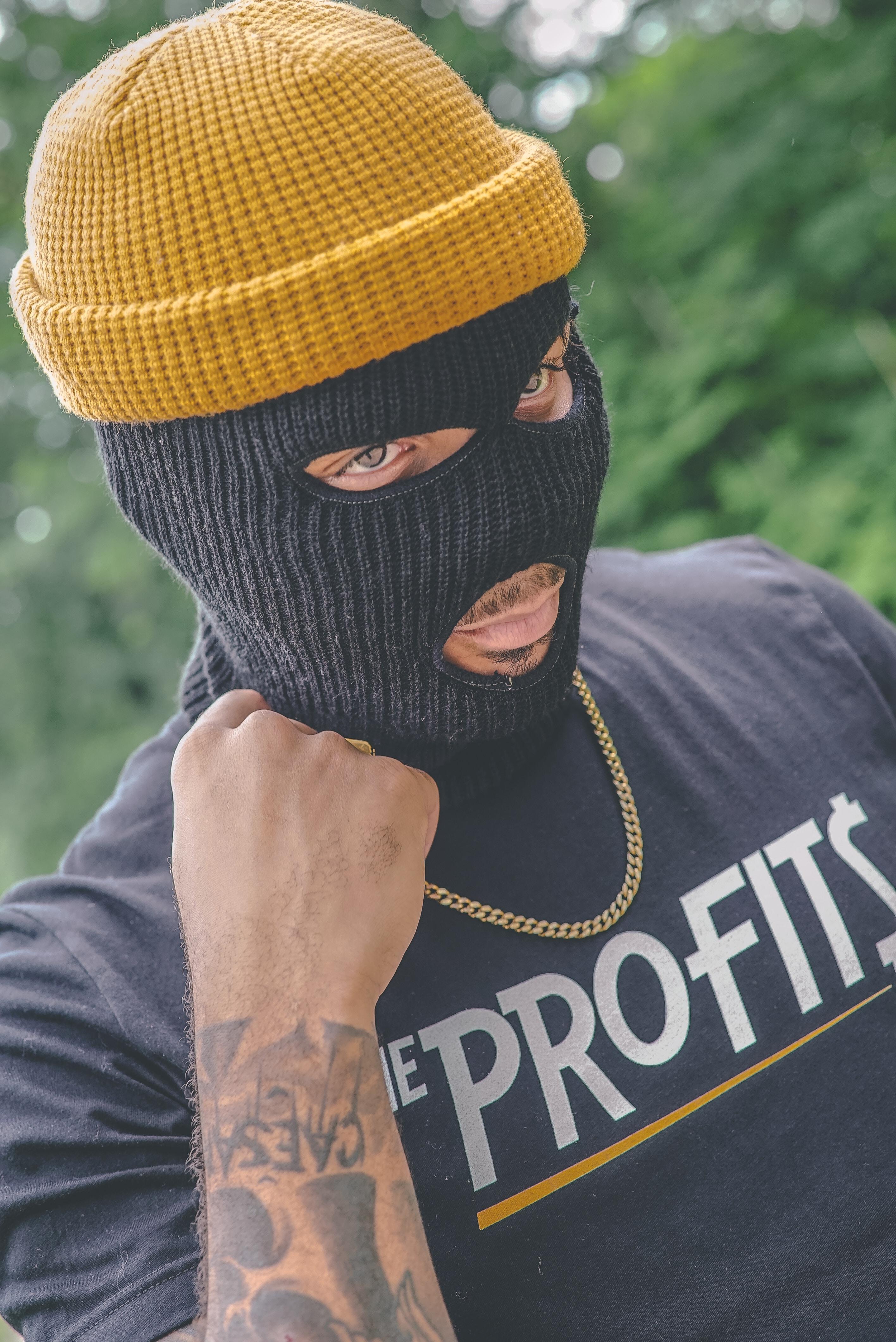 man wearing black balaclava mask and brown knit cap outdoor during daytime