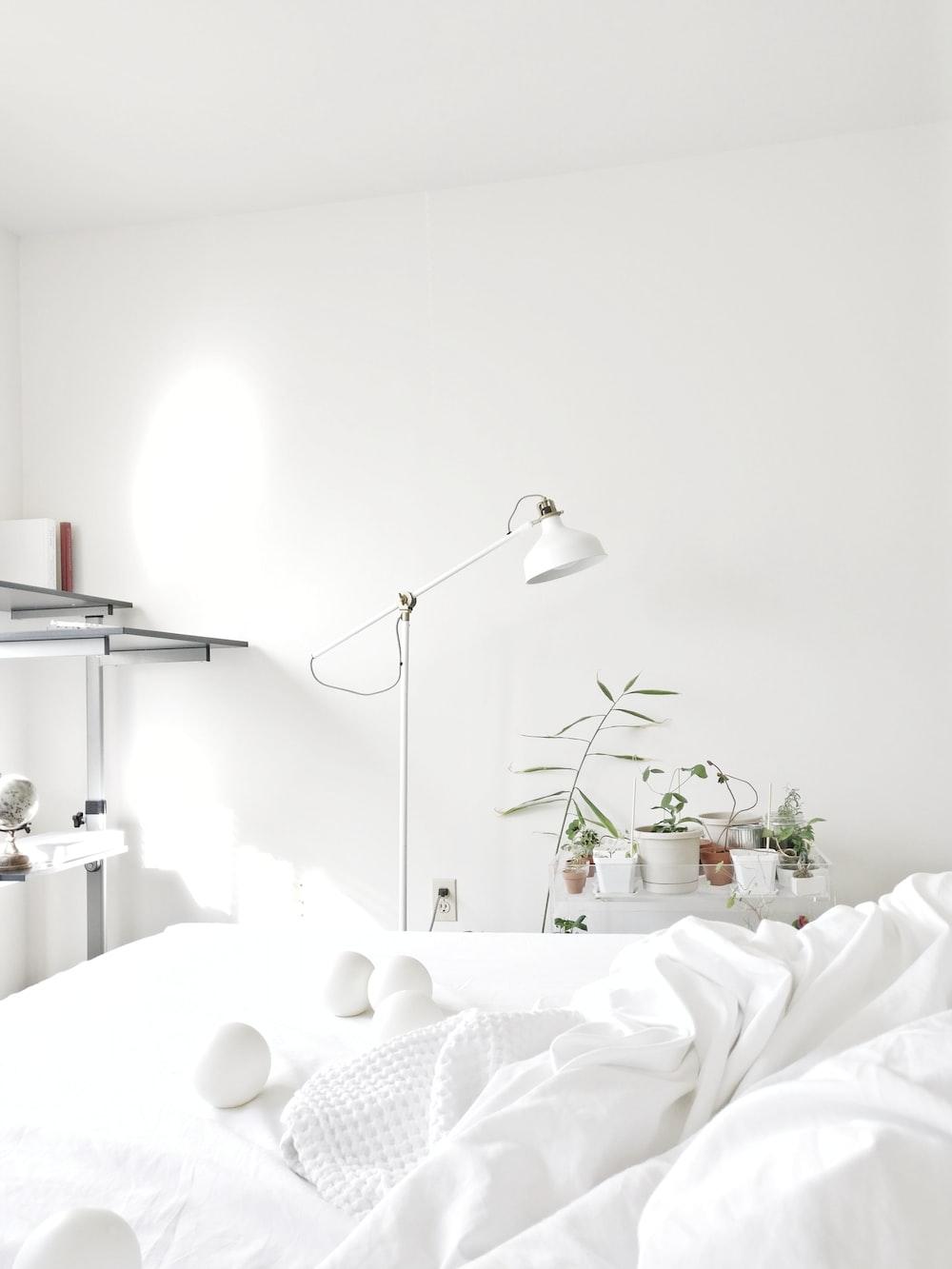 powered-off floor lamp beside comforter