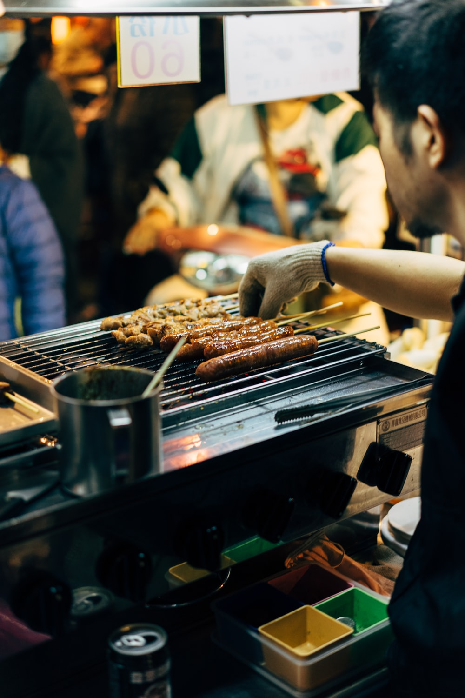 man barbecuing skewered sausages