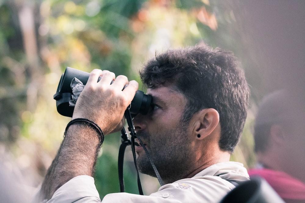 man using black binoculars at daytime