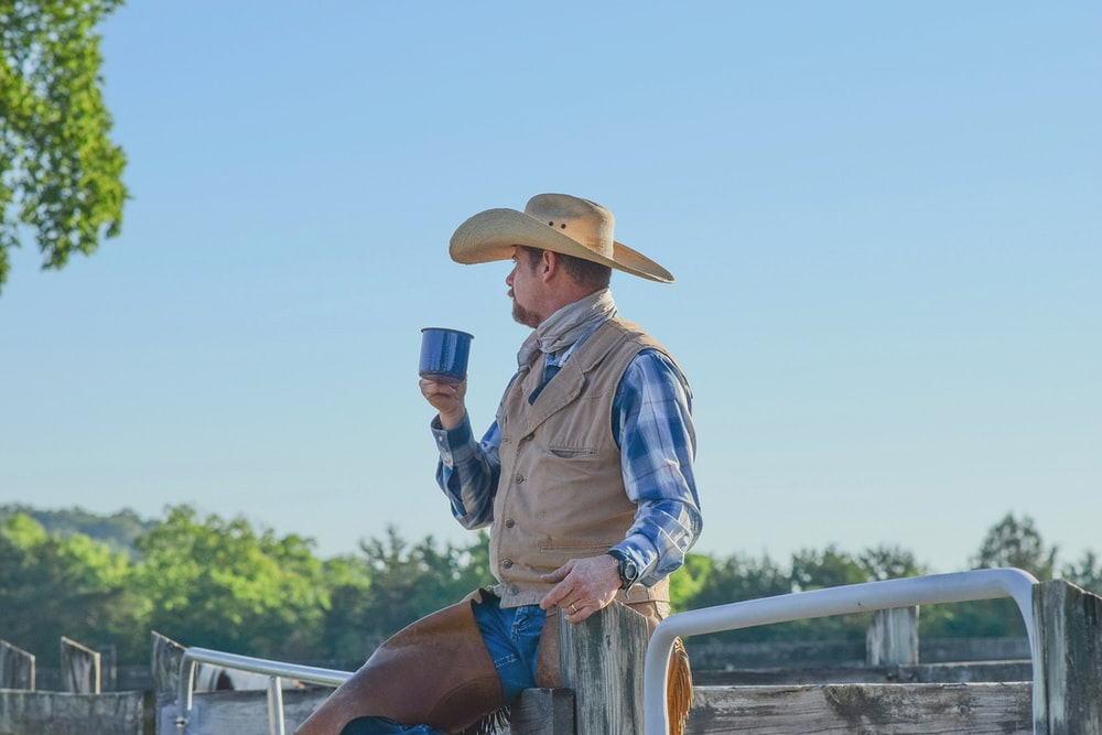 man standing while holding blue cup
