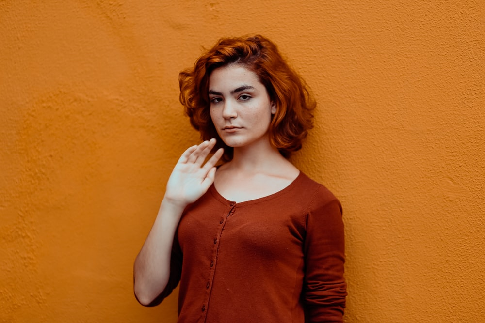woman in red button-up shirt leaning orange wall