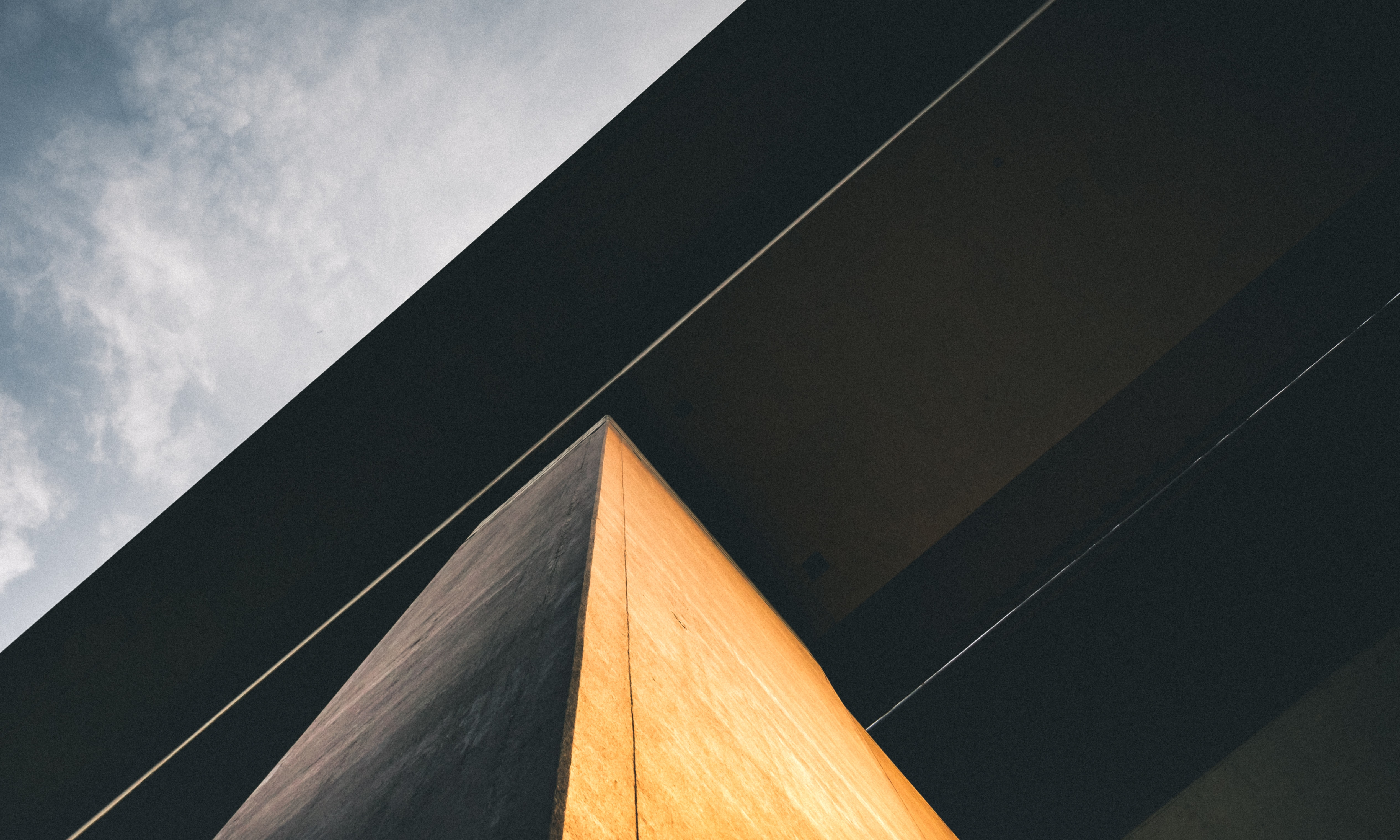 low-angle photography of black and brown concrete building under cloudy ble sky