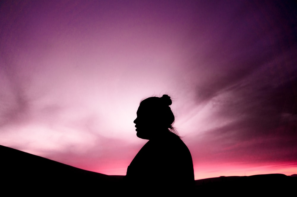 silhouette of woman under purple sky