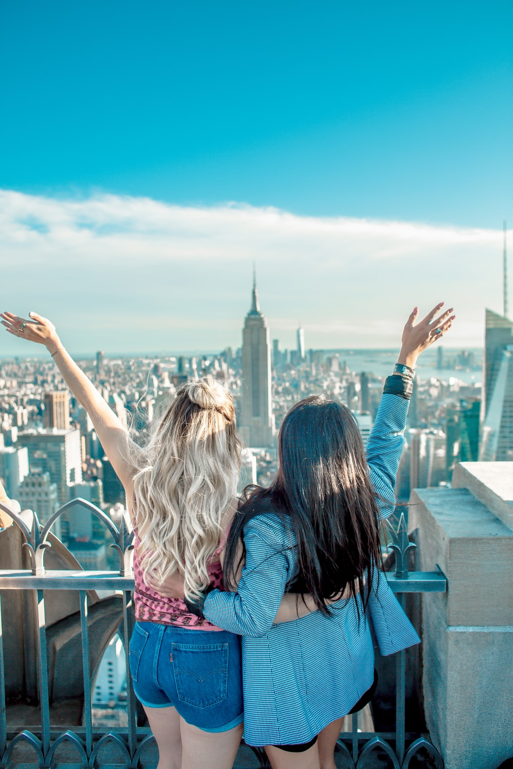 two women hands on their back while raising their hands facing Empire State building