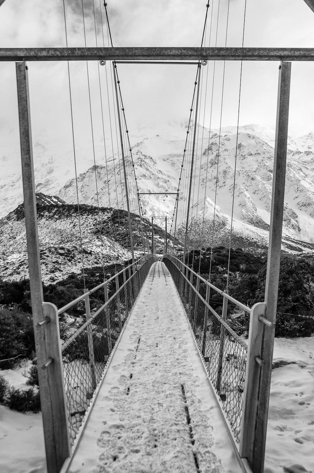 grayscale photo of bridge near mountain