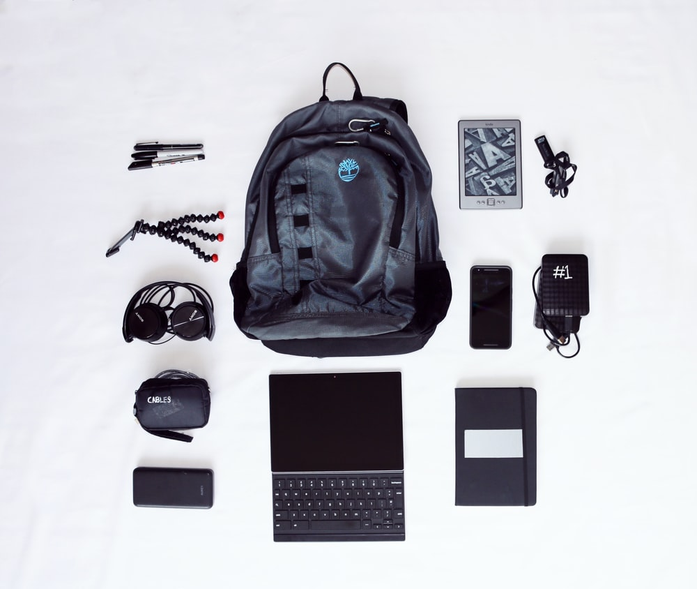 flat lay photography of backpack, laptop computer, headphones, smartphone, and octopus tripod
