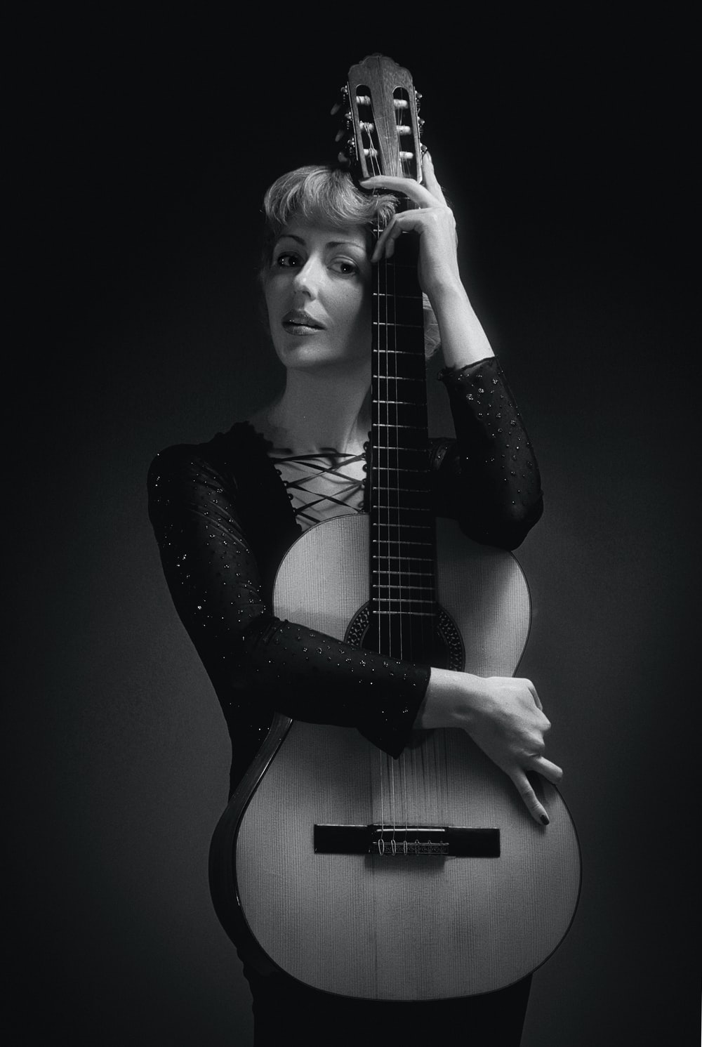 grayscale photography of woman holding guitar
