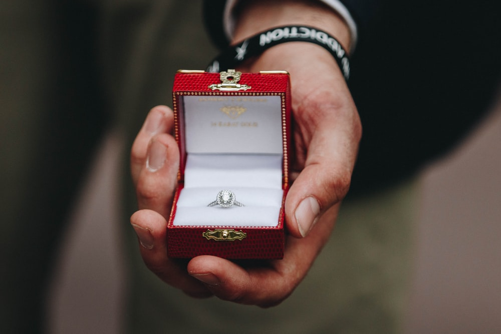person holding box of silver-colored ring with clear gemstone