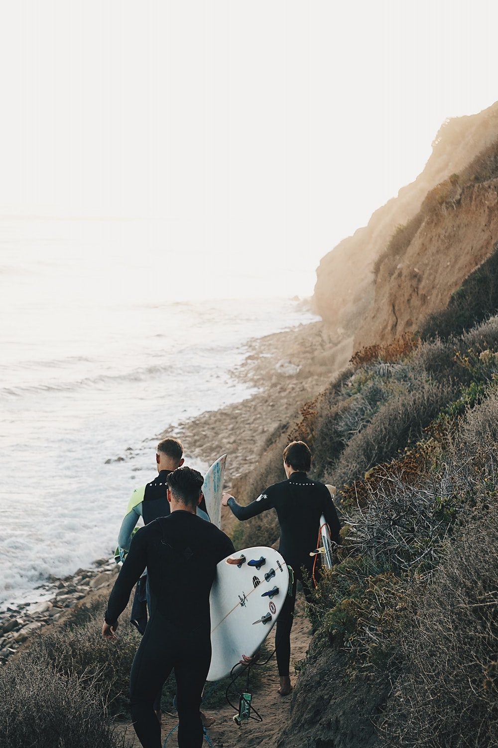 three men holding surfboards