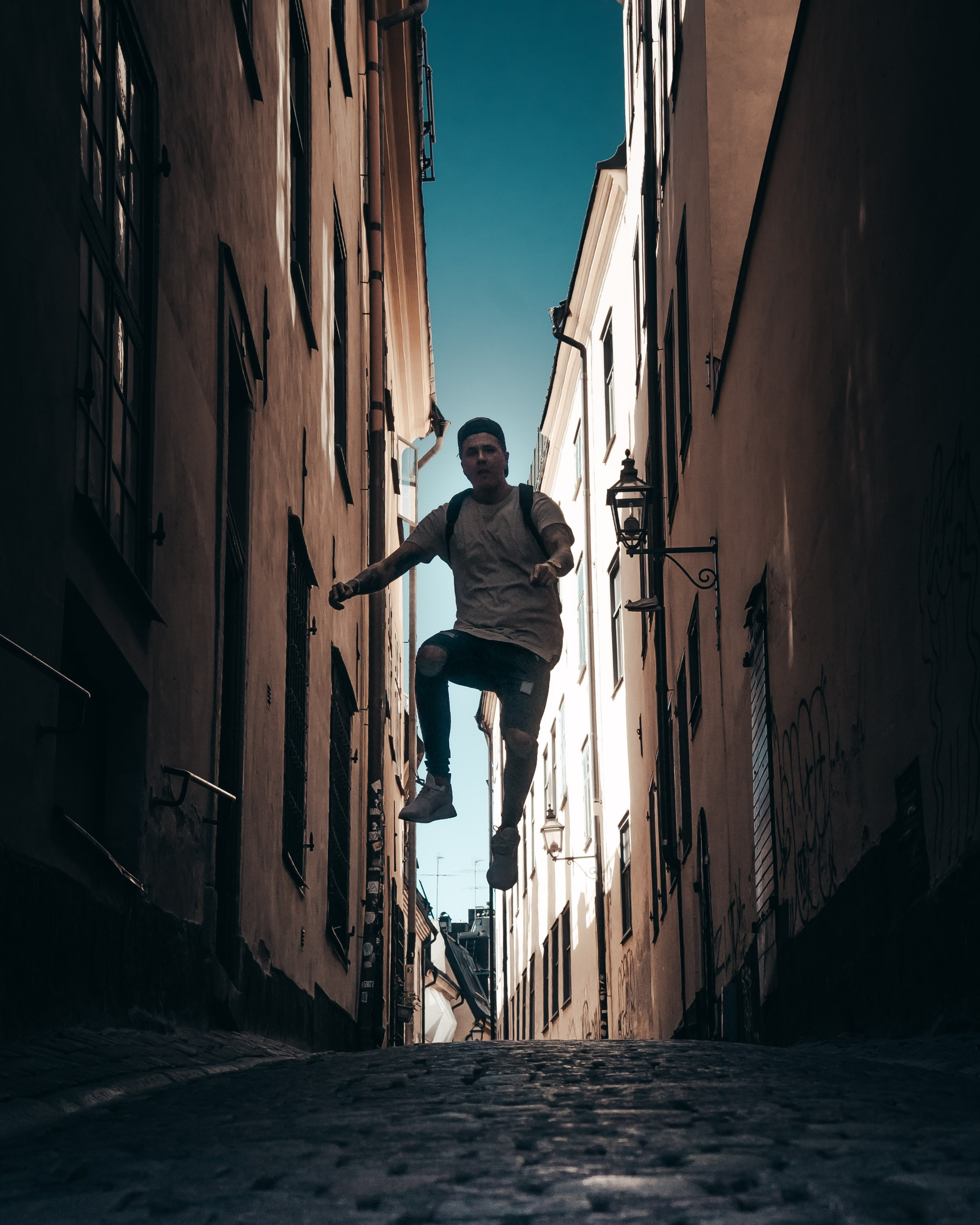 man jumping in middle of brown buildings