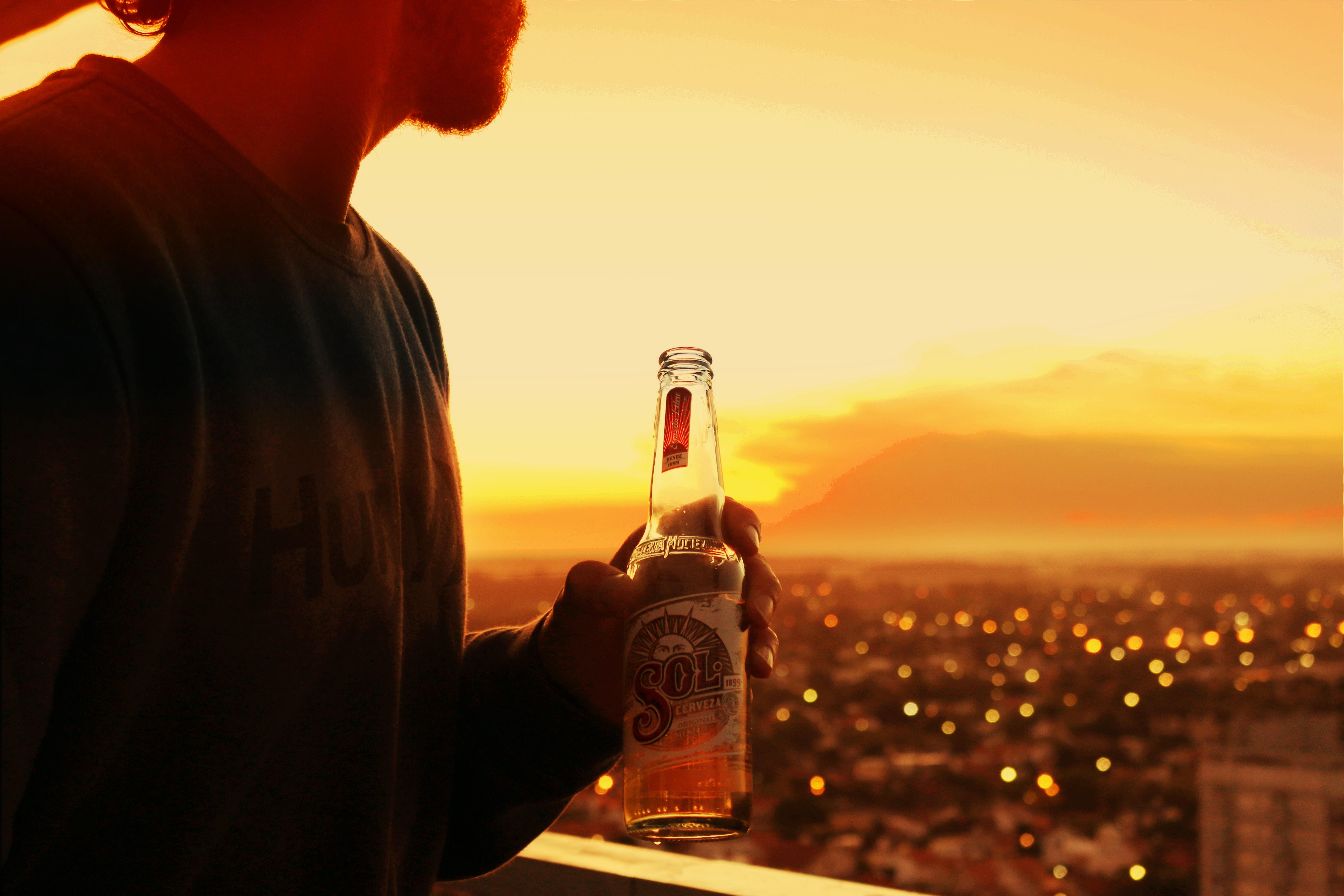 man holding bottle near buildings