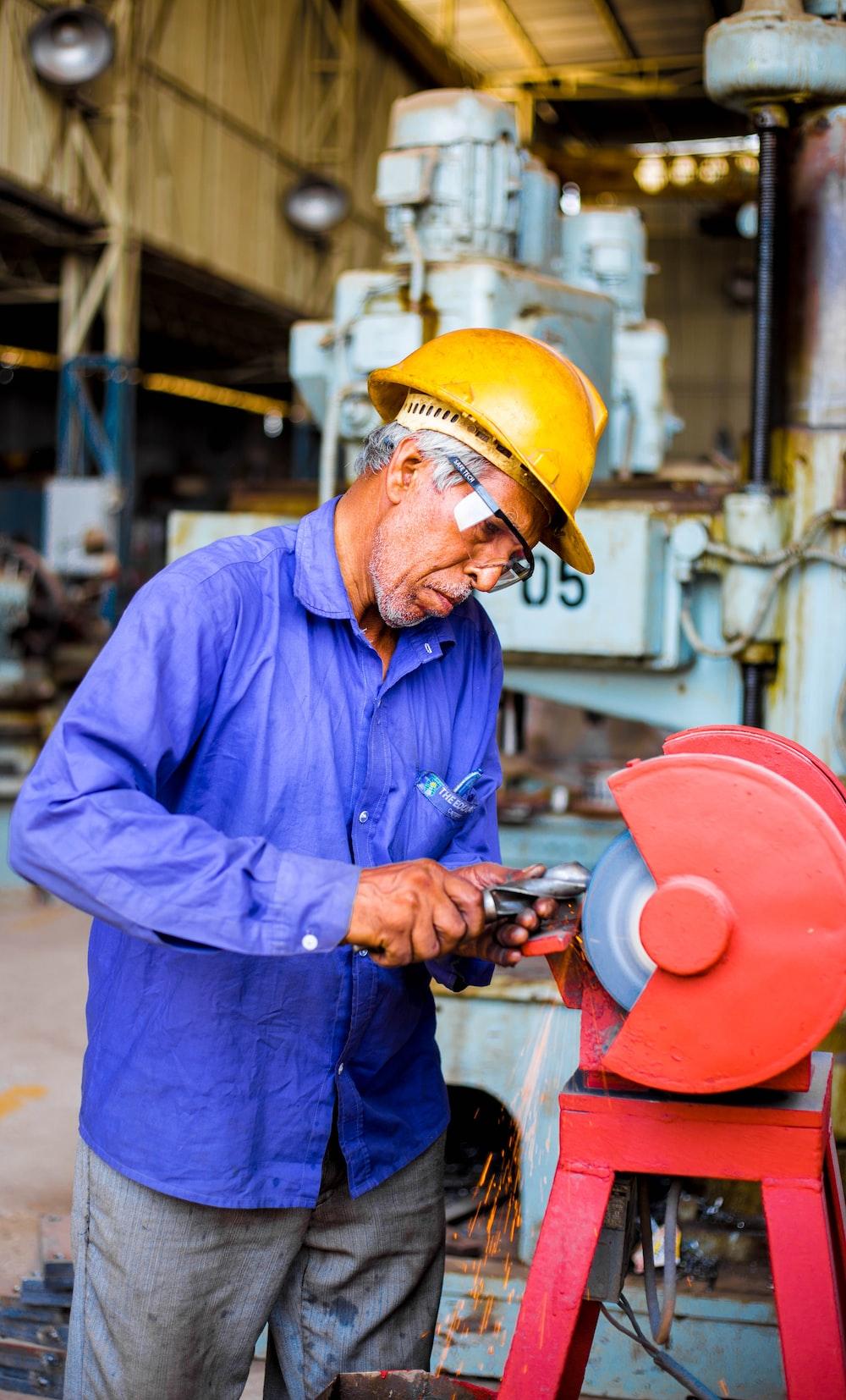 man grinding metal tool in industrial machinery