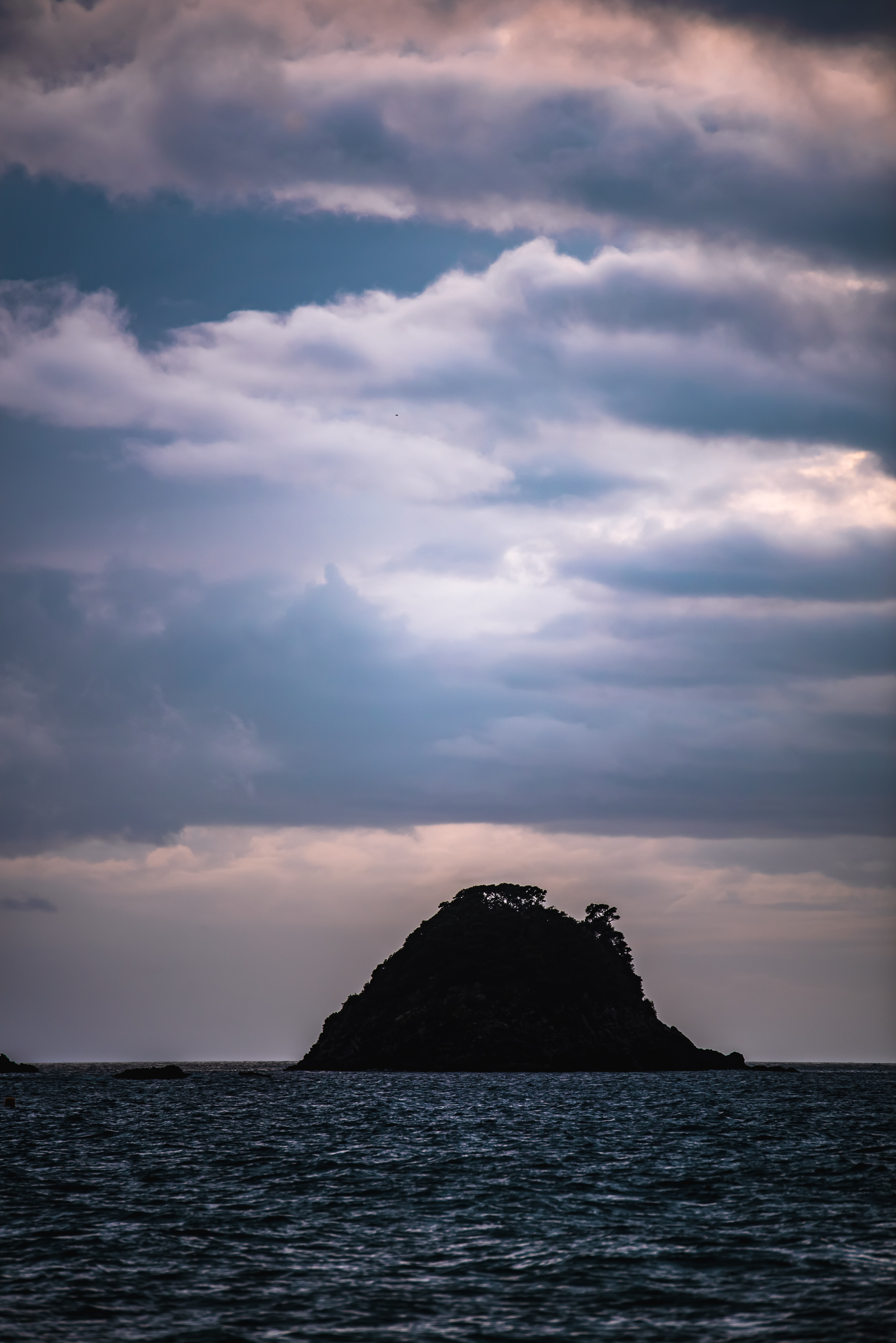 silhouette of island under cloudy sky