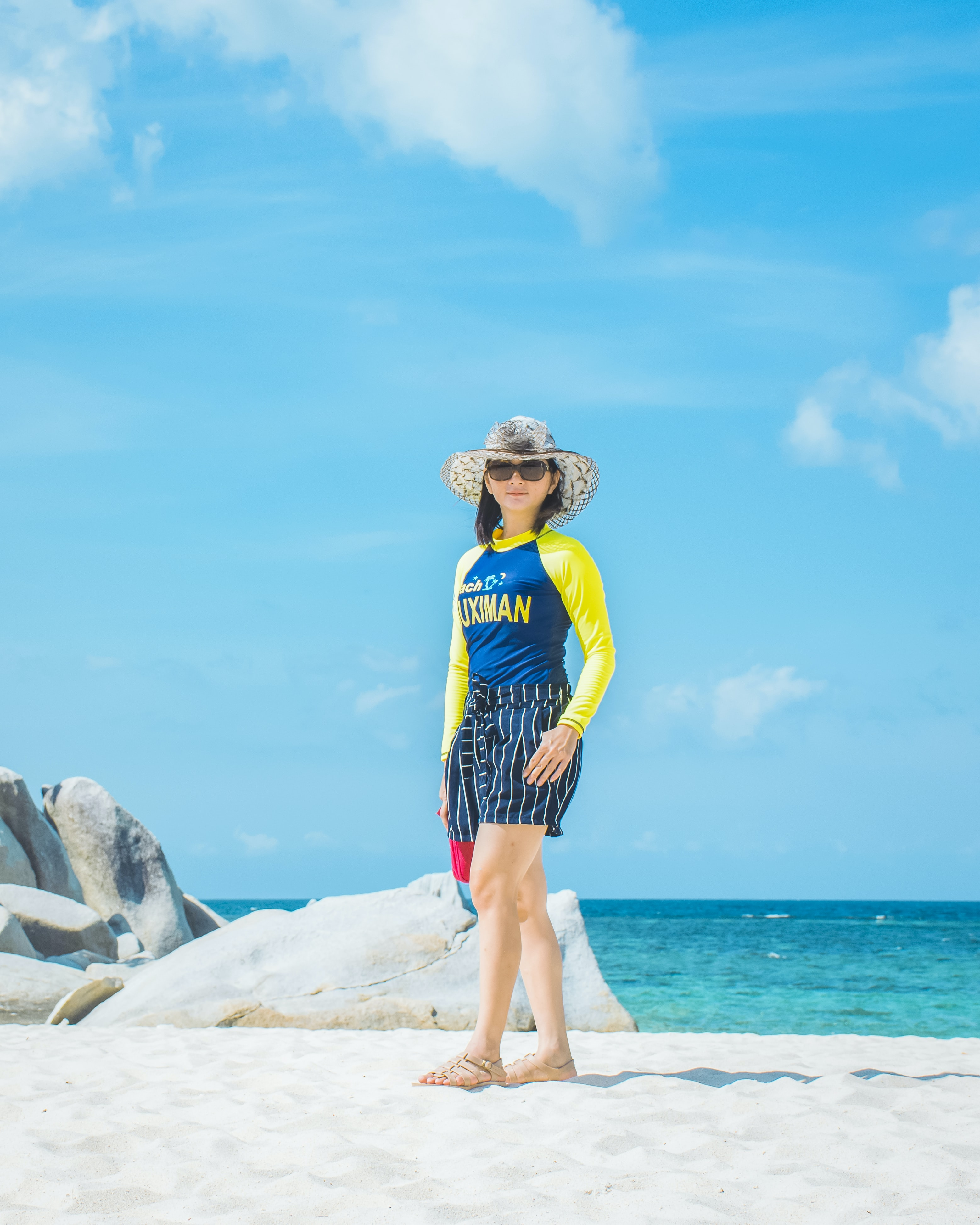 woman with eyeglasses standing on white sand near shore during daytime