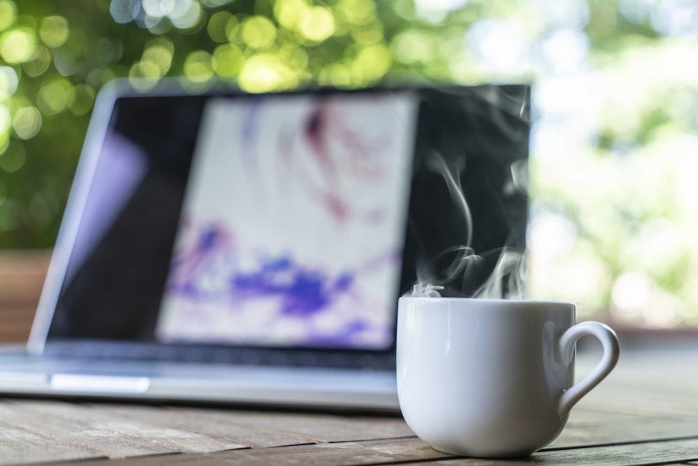 shallow focus photography of white ceramic mug near laptop