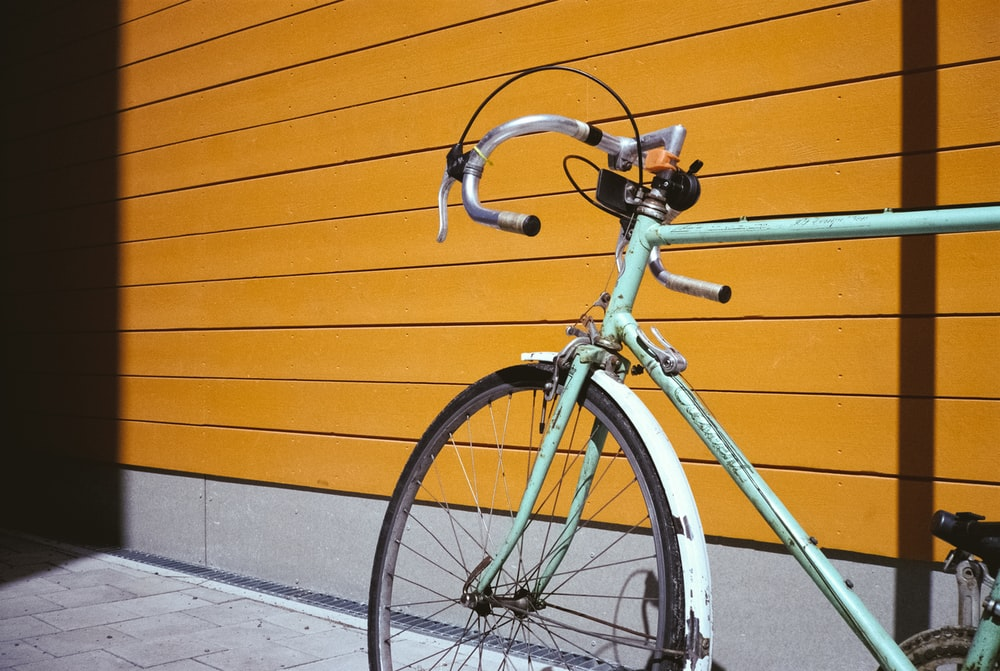 teal road bike parked beside brown wall