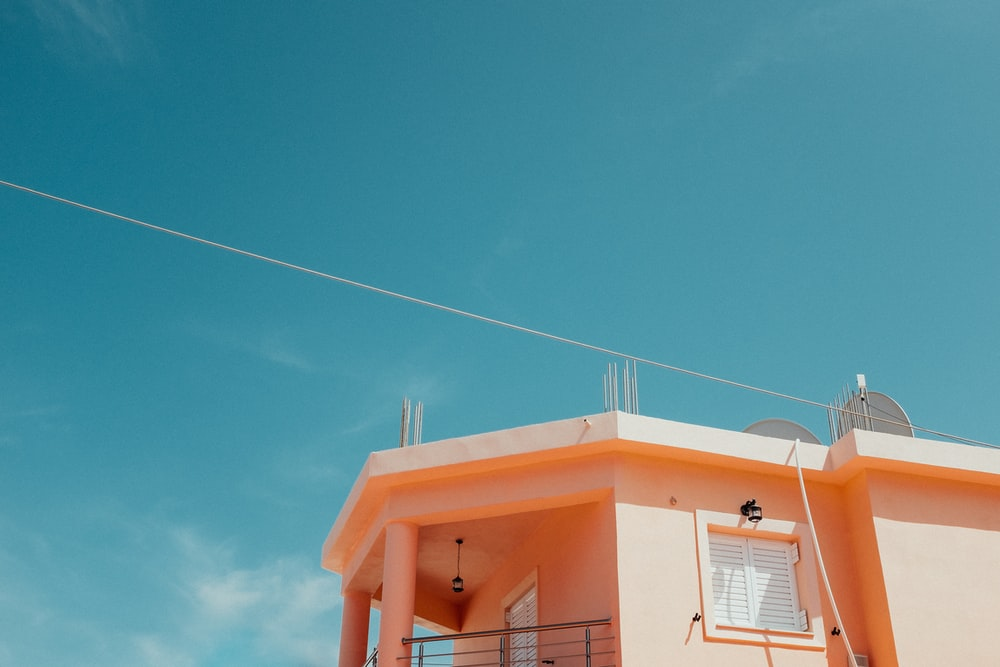 orange and white house under blue sky during daytime