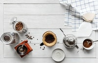 flat lay photography of coffee press, mug, and coffee grinder