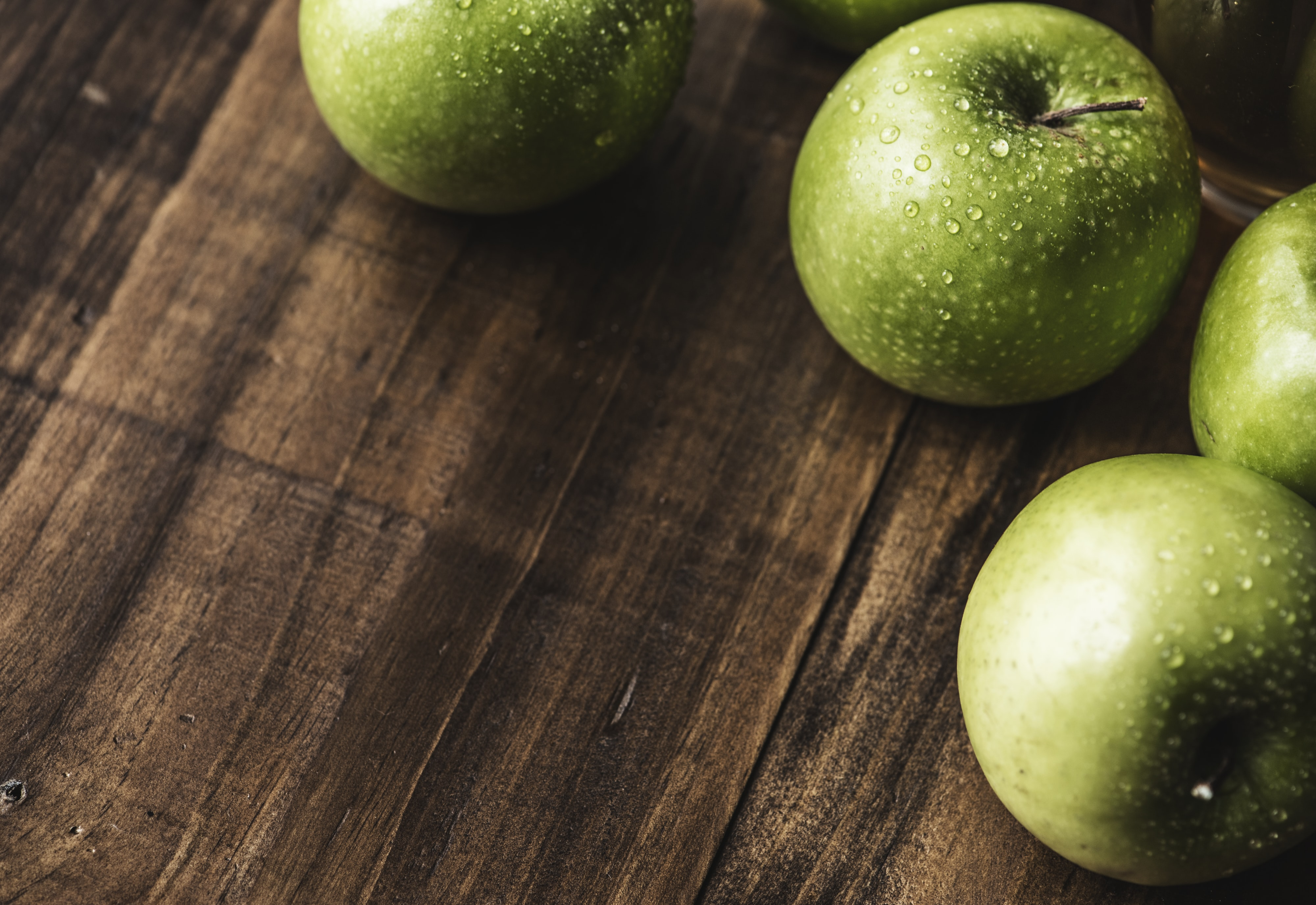 four green apples on wooden surface