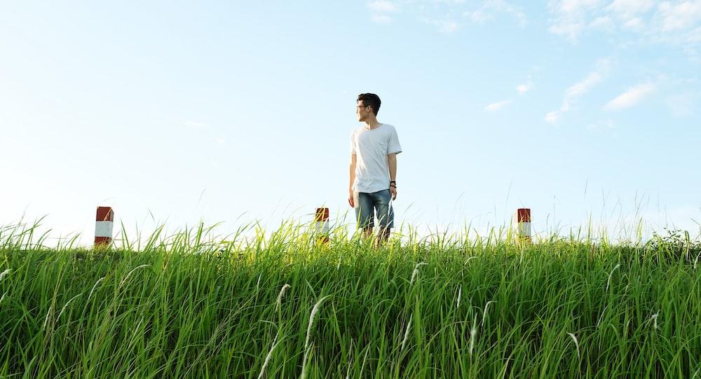 man in white shirt standing on green grasas