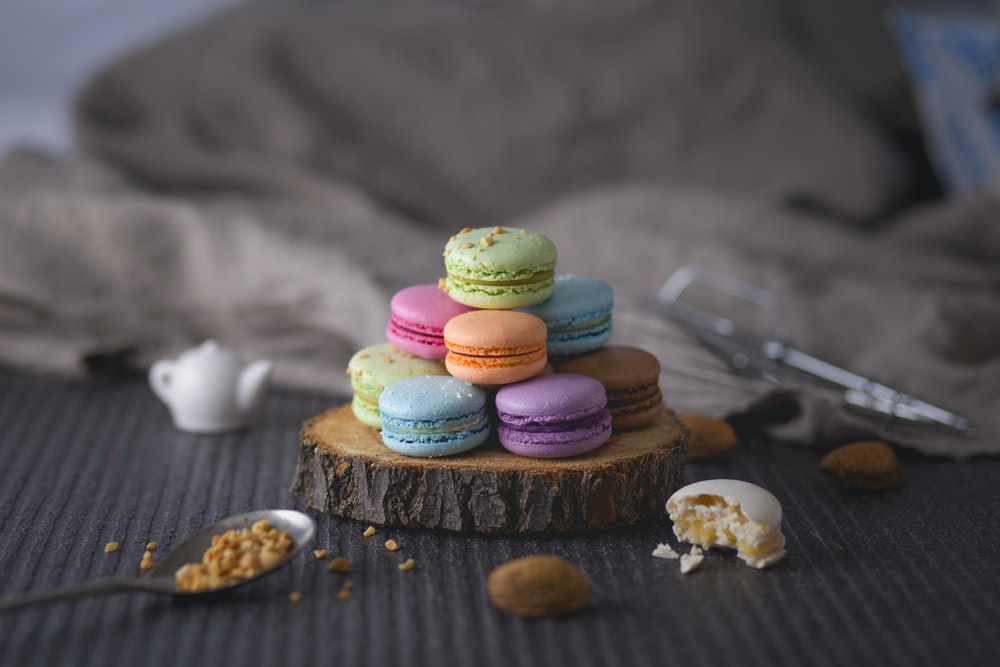 assorted-color macaroons on wood slab