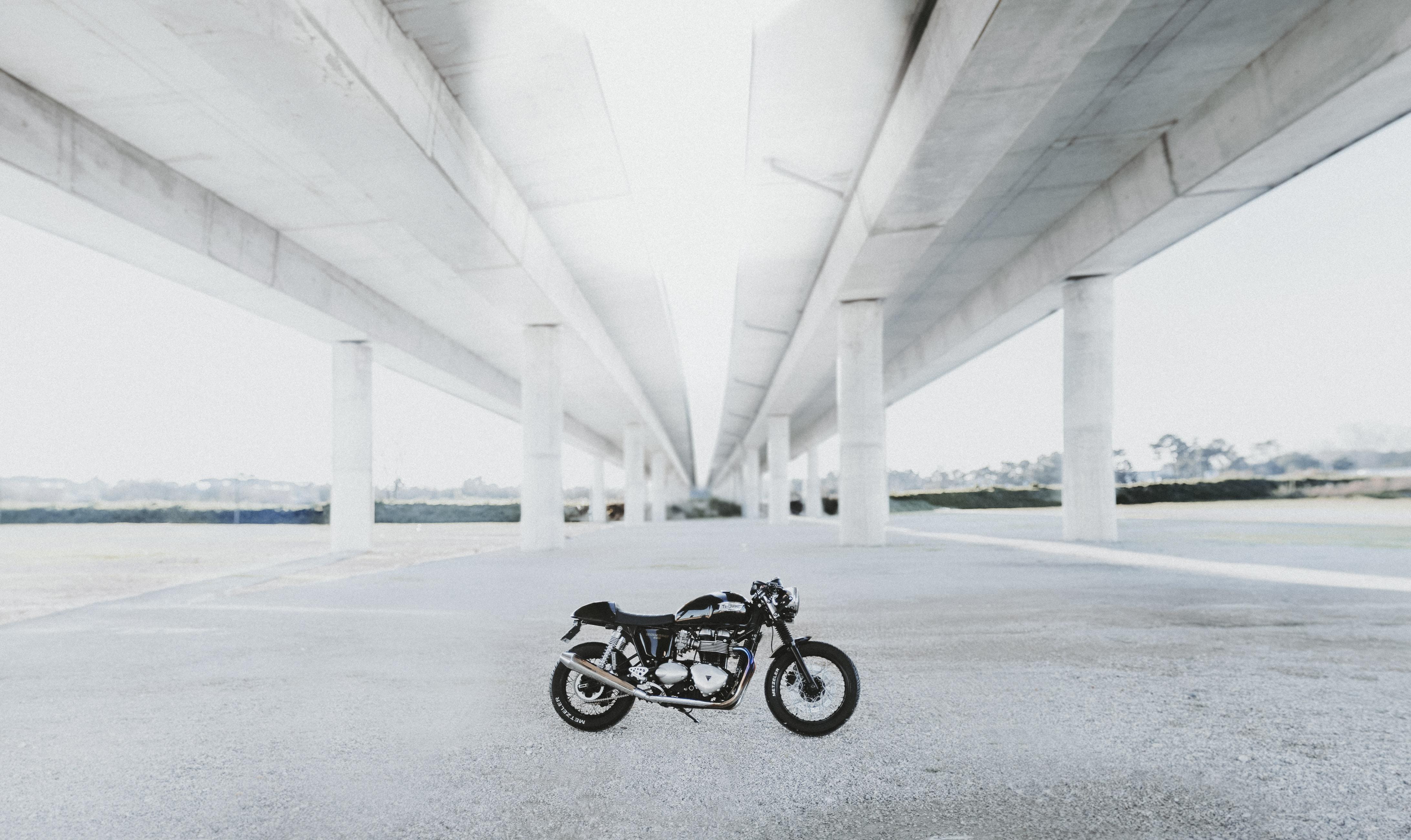black naked motorcycle under white bridge during daytime