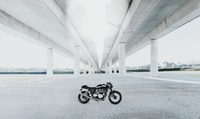 black naked motorcycle under white bridge during daytime