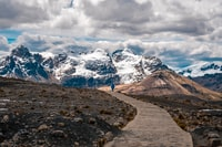 person walking toward snow-capped mountain