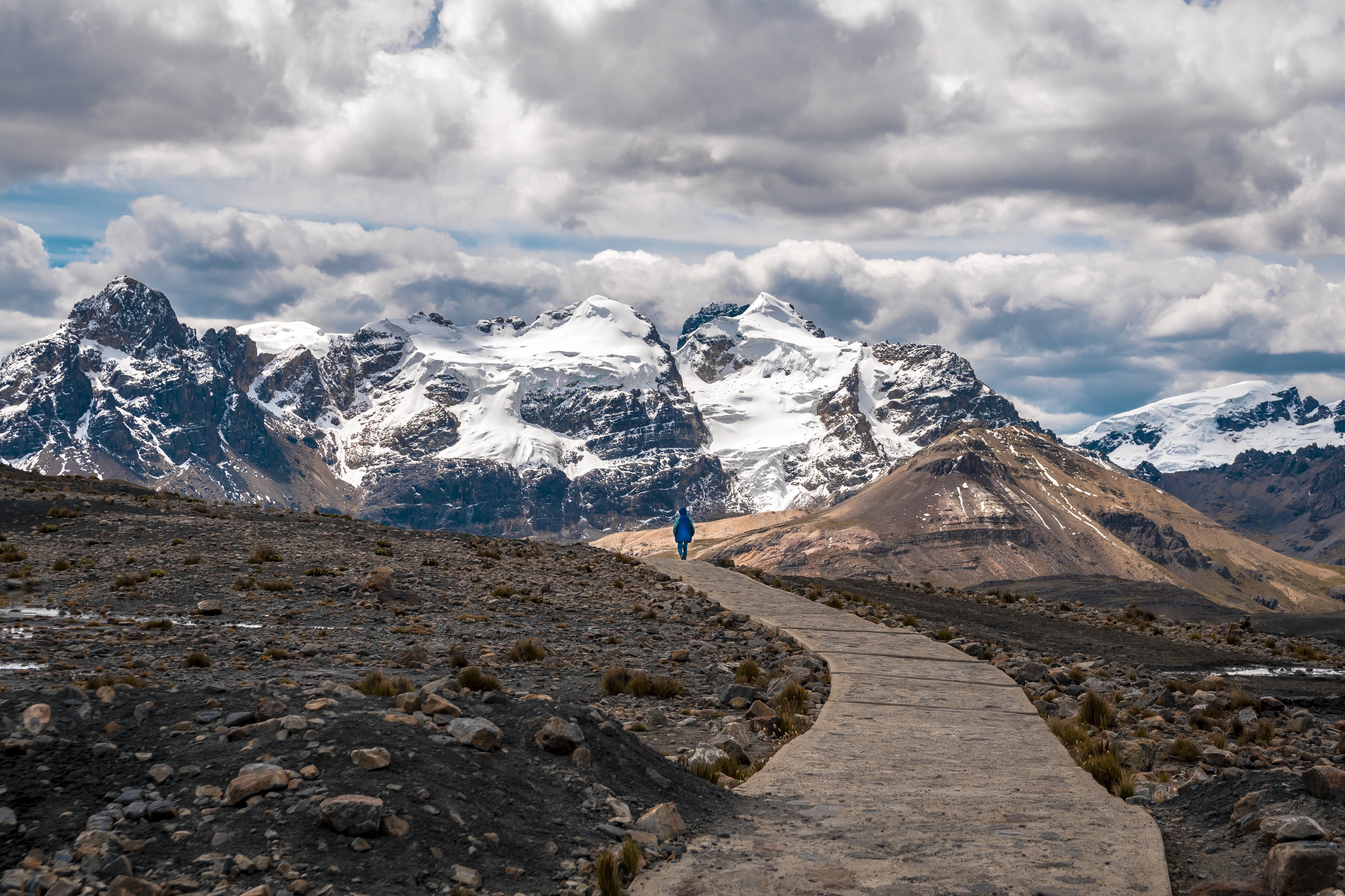 person walking toward snow-capped mountain