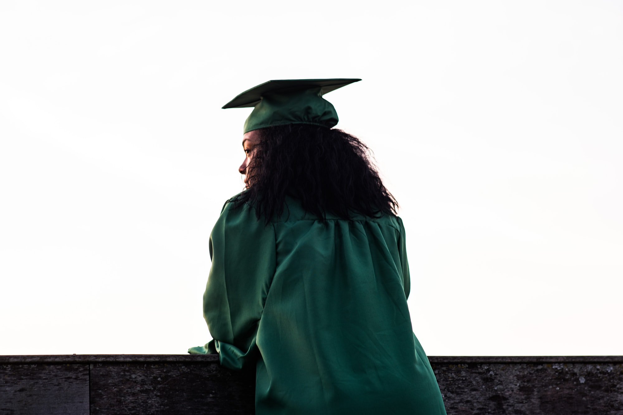 A student in her graduation gown looks out over a wall.