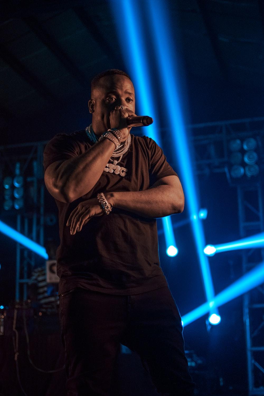 man holding microphone near spot lights