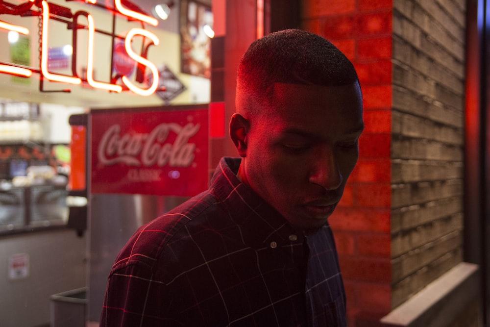 man wearing black dress top beside Coca-Cola sign
