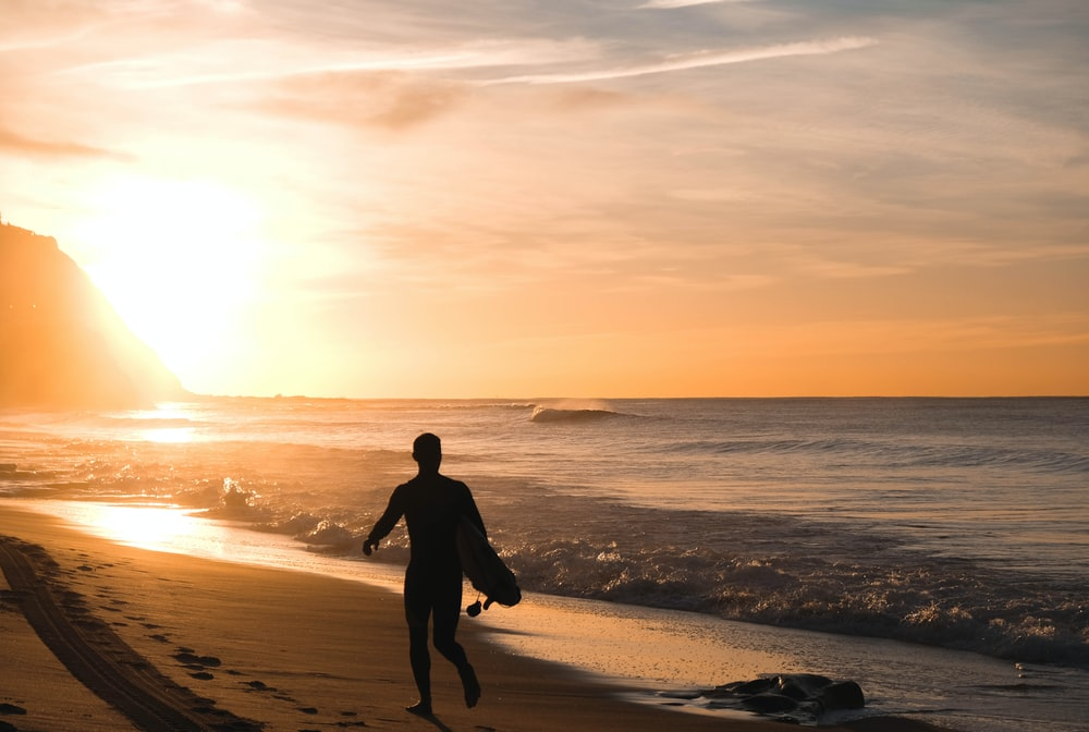 silhouette of man carrying surfboard running on shore