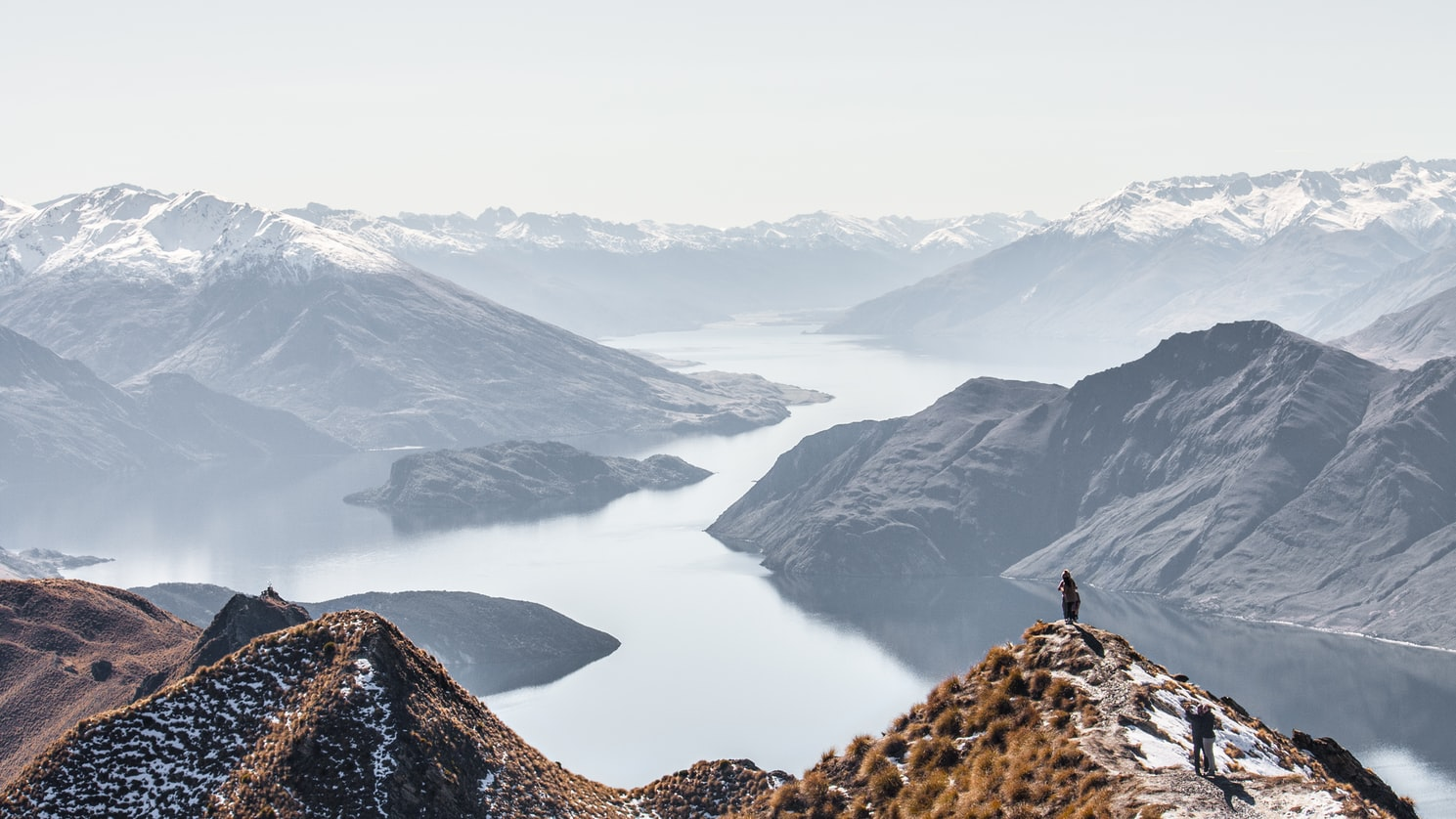 snowy capped mountains and deep fjords of New Zealand.  A person on top of a mountain in the foreground looks down on the fjord which is filled with mist.