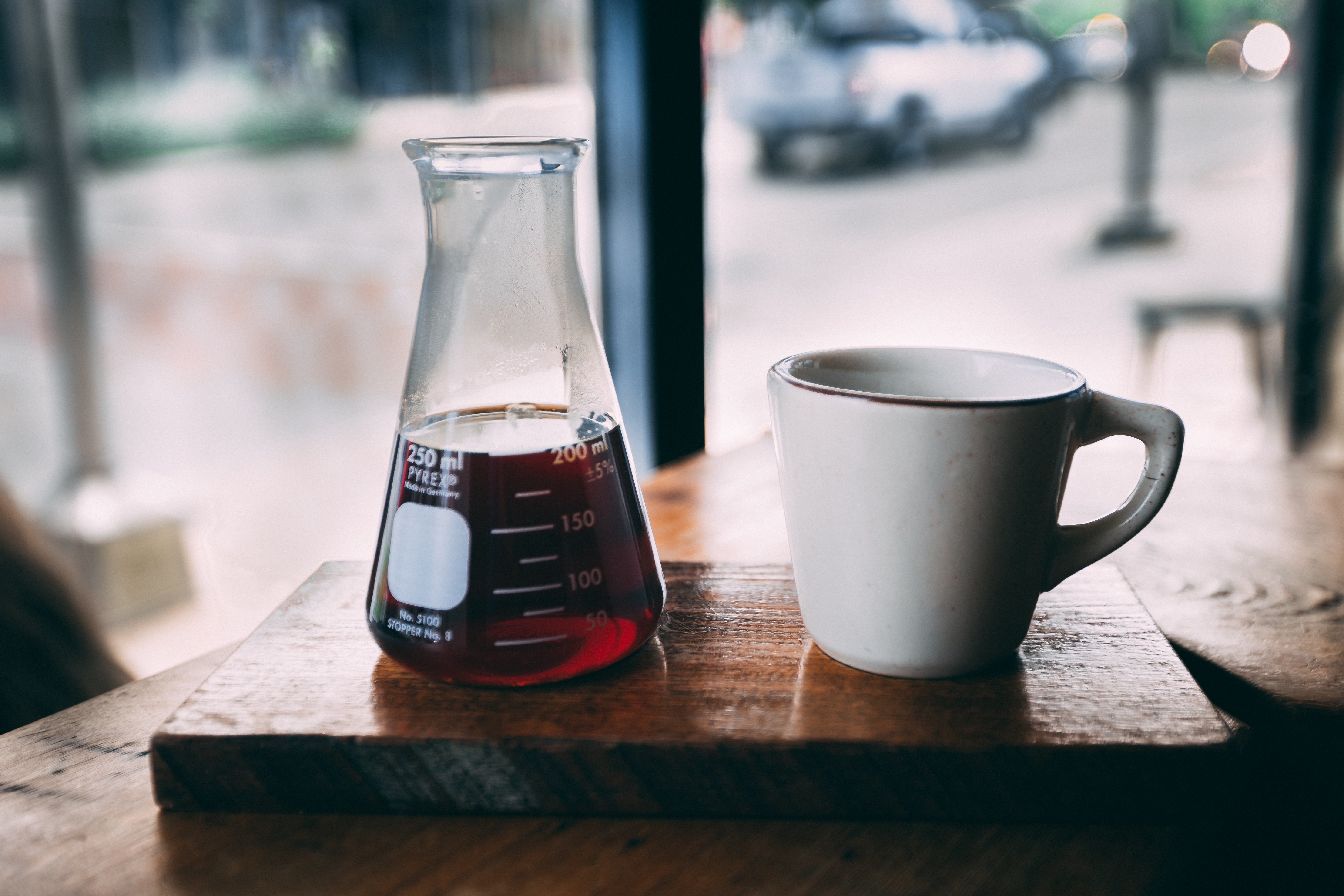 erlenmeyer flask and white ceramic mug on brown wooden table