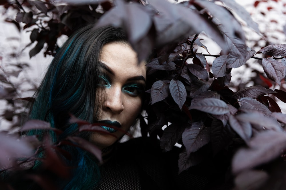 woman with green lipstick surrounded with plants