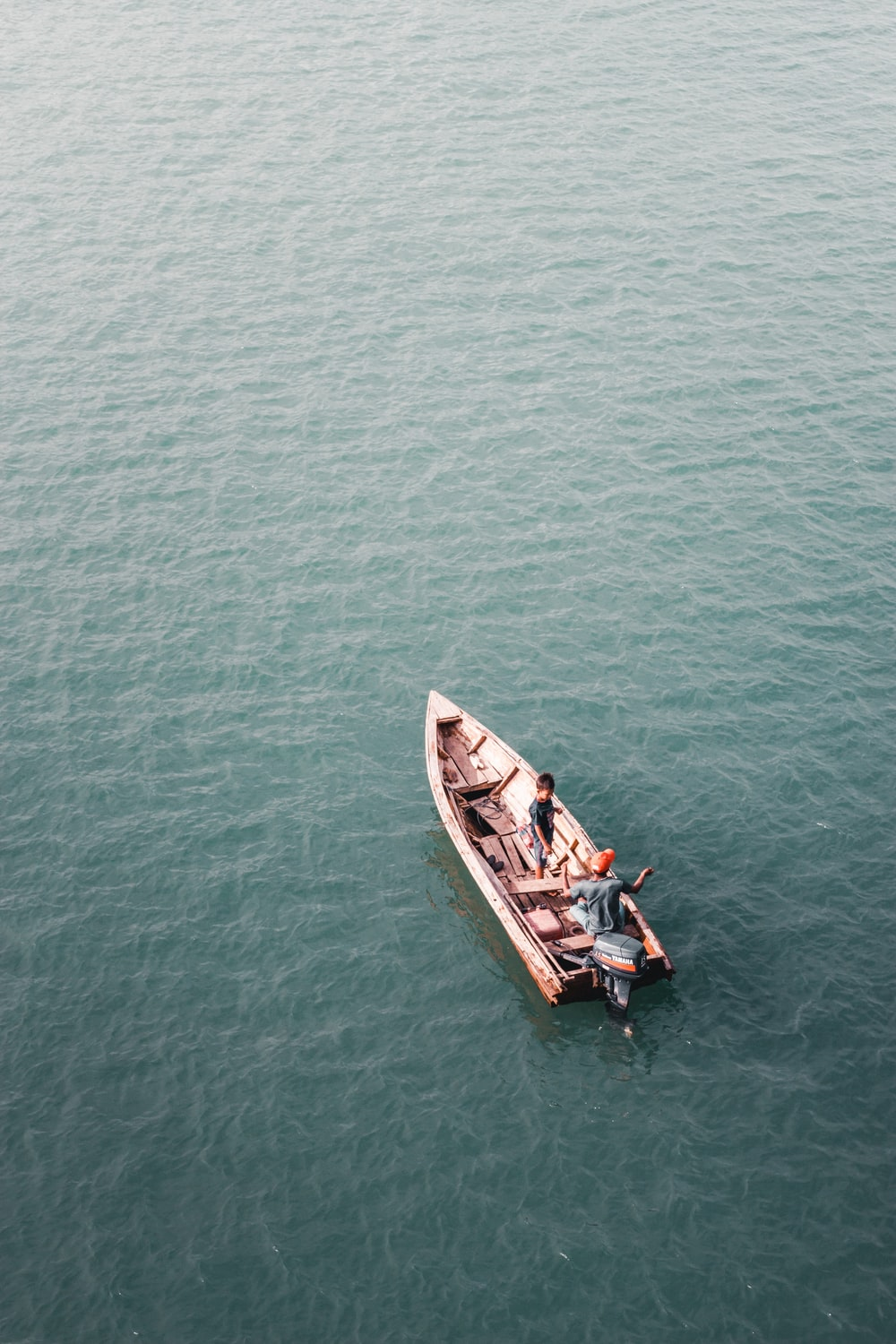 man and boy sailing on brown wooden boat during daytime