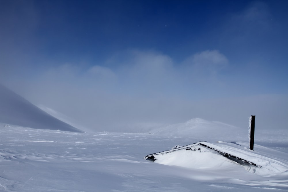 snow field under blue sky and white clouds