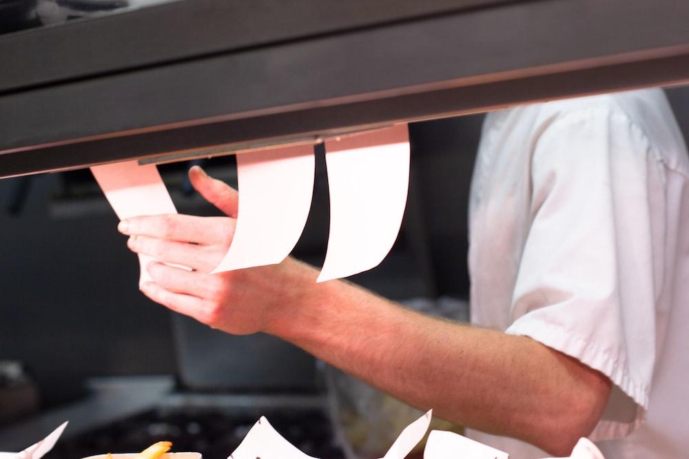 man holding white menu