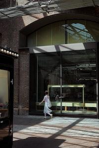 woman walking near glass window