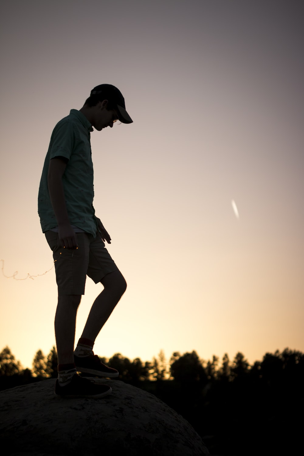 man standing on rock under clear sky