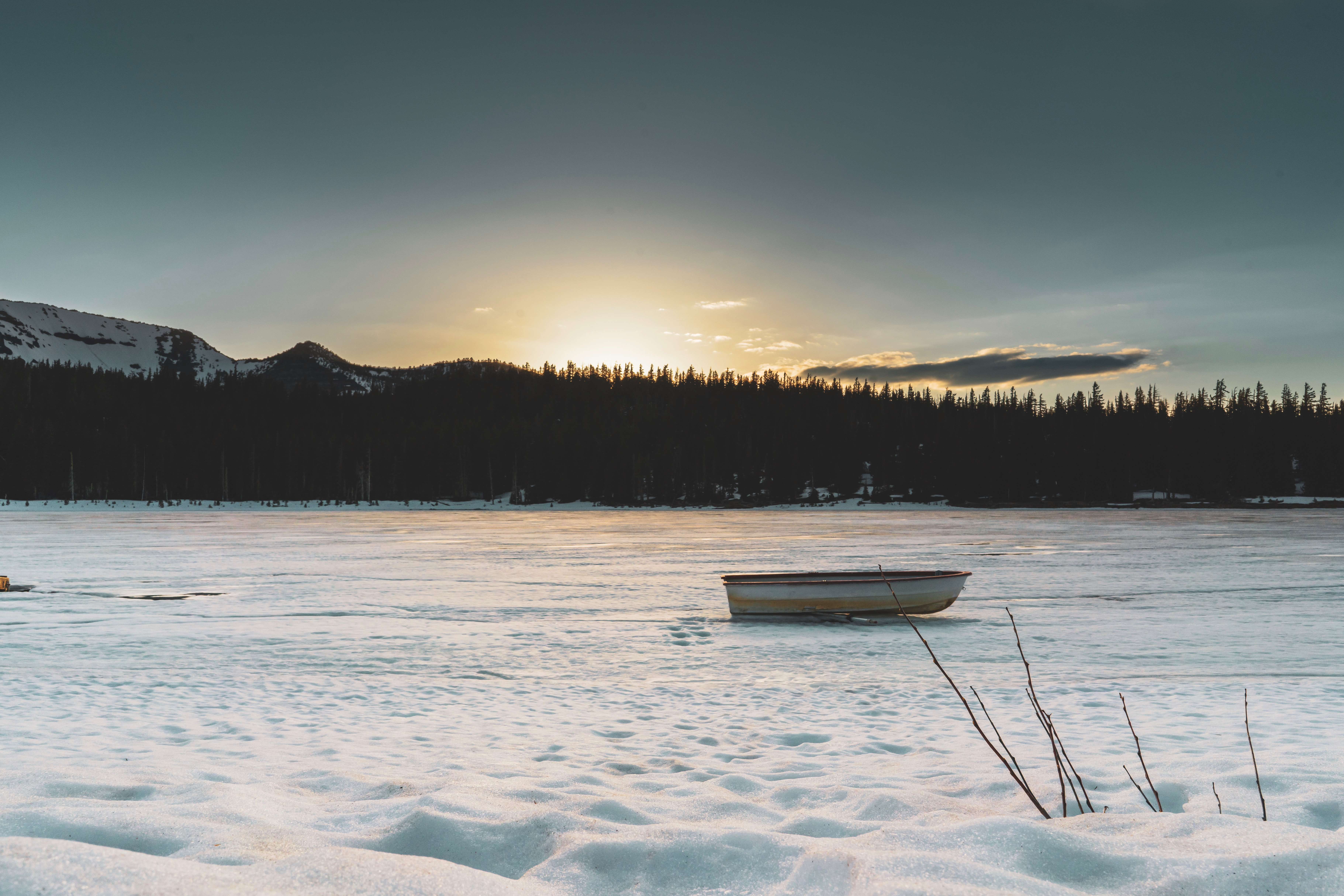 boat on frozen lake with silhouette of trees at distance